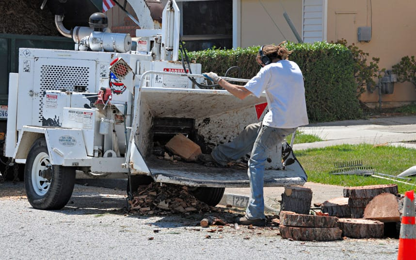 worker trying to kick wood into a chipper in an unsafe and unprotected way (how not to use a wood chipper)